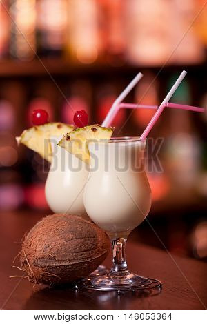 Pina Colada cocktails shot in a bar in dim light.