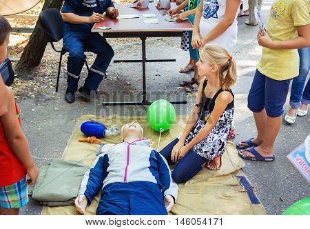 Zaporizhia/Ukraine- September  3, 2016: Charity festival for children - City of professions . Teen girl sitting near mannequin, listening first aid and CPR instructions, emergency training outdoors