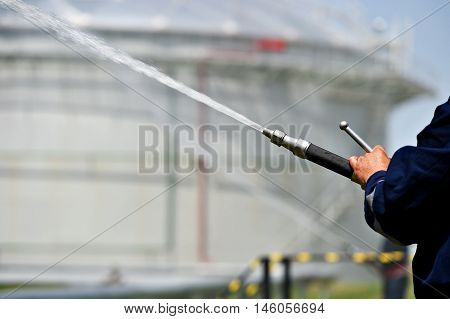 Firefighter holding high pressure water hose extinguishing a fire started near a petrol storage tank