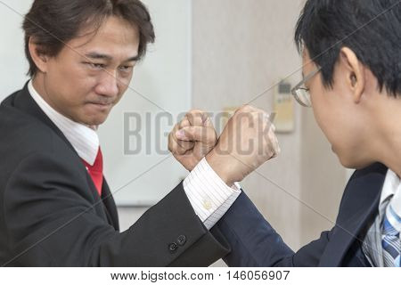 Two Businessman Competing In Arm Wrestling Competition concept