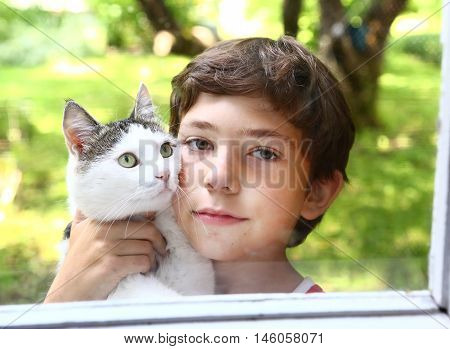 preteen handsome boy with cat close up photo through the window on the summer garden background