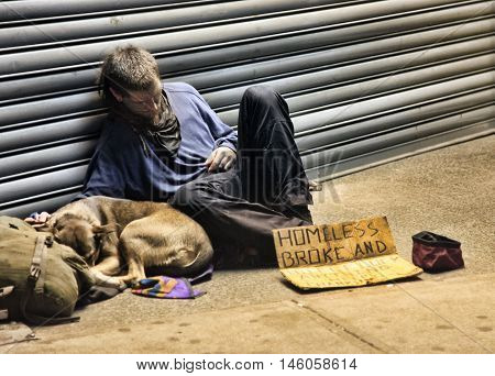 New York USA - May 16 2013: homeless man sleeping with dog on sidewalk on 8th Ave and 42th Street Manhattan NY.