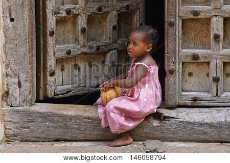 Stone Town Tanzania - December 30 2015: Traditional house with old door and small girl sitting on the street of Stone Town.