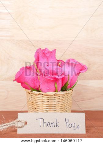 Handwriting Thank you on brown label and bouquet of pink rose flower with wood background