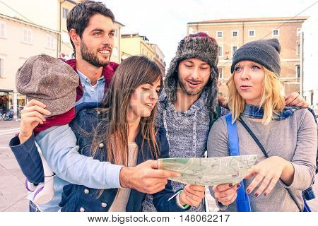 Group of friends looking map in old town day tour - Teenagers on holiday talking each others searching direction - Concept of young tourists traveling together lost in the city - Soft vintage filter