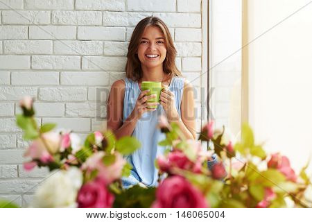 Horizontal close-up portrait of joyful and laughing softly young girl sitting on the window-sill and drinking a cup of coffee against a flowered foreground