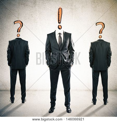 Two question mark headed businesspeople behind exclamation mark headed man on textured concrete background. Leadership and management concept