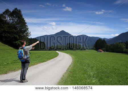 hiker is showing to beautiful natural landscape