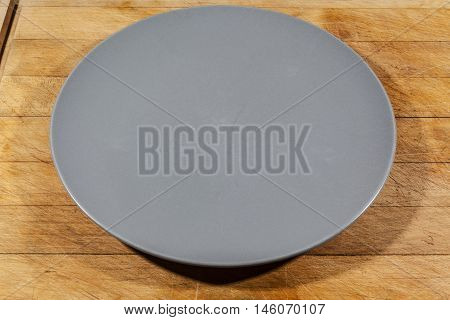 Flat grey ceramic plate on wooden cutting board from side