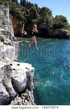 young girl is jumping in the blue sea