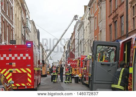 LONDON UNITED KINGDOM - JANUARY 28: Fire Brigade Fights With Flames in London on JANUARY 28 2013. Fire Fighters With Equipment in Albemarle Street in London United Kingdom.