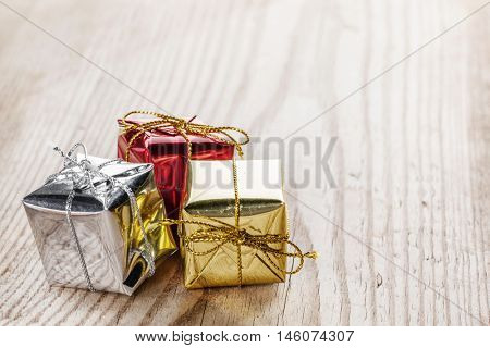 Small gift boxes on wooden background macro