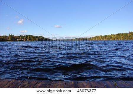 the edge of the wooden pier, the pier, the waves, deep blue water of the lake, a little Cumulus clouds, a forest on the horizon