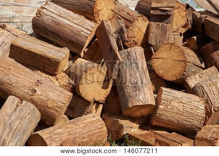 The picturesque pile of wooden chump from old logs. The logs are damaged by larvae butterfly carpenter. Background