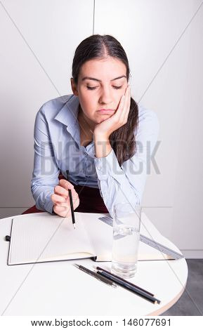 young business woman is sitting bored in the office