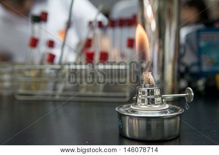 Close-up detail of an ethanol burner also known as a spirit lamp in a microbiological laboratory with test tubes in the background. Science concept.