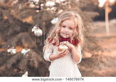 Funny baby girl wearing knitted scarf and shirt holding glitter christmas ball standing over christmas tree outdoors.Looking at camera. Posing outdoors. Holidays time. Childhood.