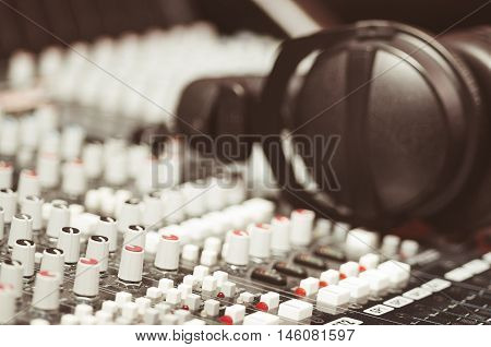 Closeup mixing console with headphones on top, faders and knobs background, artistic studio equipment concept.