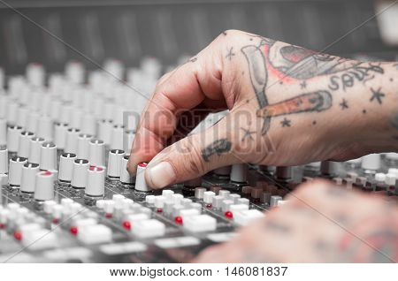 Closeup of hands covered with tattoos working on mixer console, twisting knobs, studio equipment concept.