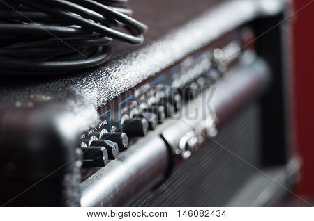 Closeup amplifier with row of buttons and knobs, descriptions turning blurry, cable bundle placed on top, studio equipment concept.