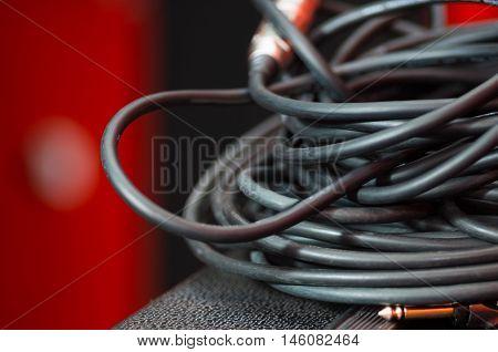 Closeup standard black audio cables rolled into bundle, studio equipment concept.