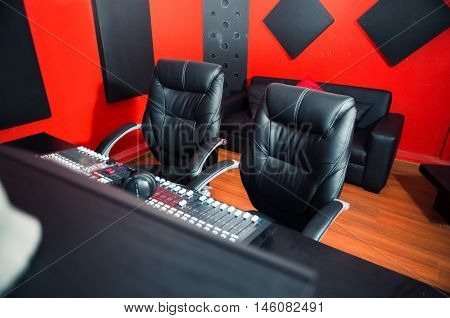 Classy professional recording studio setup, large desk with mixing console and two chairs, window for vocal booth, sofa placed behind.