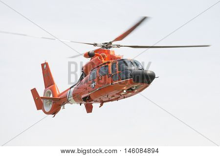 JERSEY CITY NJ MAY 29 2016: Close-up of the orange U.S. Coast Guard MH-65 Dolphin helicopter and crew performing a Search and Rescue demonstration at Liberty State Park during Fleet Week 2016.