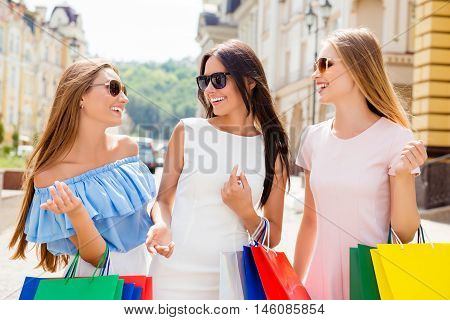Three Happy Laughing Women With Paperbags Discussing Shopping