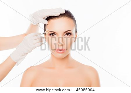Plastic Surgeon Making Botox Injection In Woman's Eyebrow