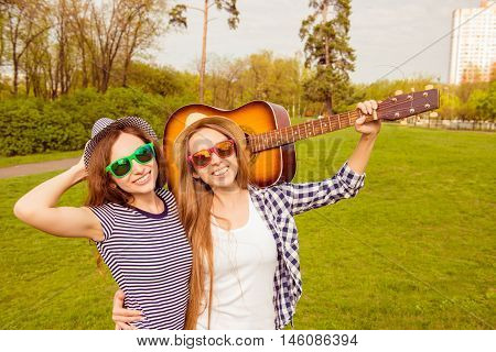 Happy Smiling Girlfriends In Spectacles Walking In The Park With Guitar