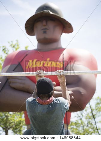 JERSEY CITY NJ MAY 29 2016: A man does chin-ups from a metal bar in front of a giant inflated balloon of a US Marine Corpsman at Liberty State Park during Fleet Week 2016.