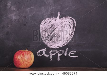 Apple On A Wooden Surface Against A Blackboard Vintage Retro Filter.