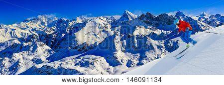 Skier skiing downhill in high mountains in fresh powder snow. Snow mountain range and Mt Fort Peak Alps region Switzerland in background.