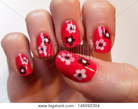 Flower art manicure. Valentines Day Holiday style bright Manicure with painted hearts and polka dots. Bottle of Nail Polish. Beauty salon. Hand. Trendy Stylish Colorful Nails, Nailpolish