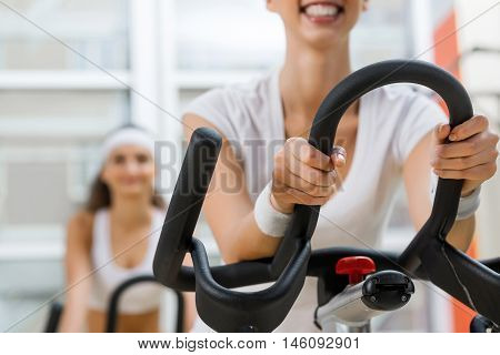 Small group of young people exercising on bikes in fitness center