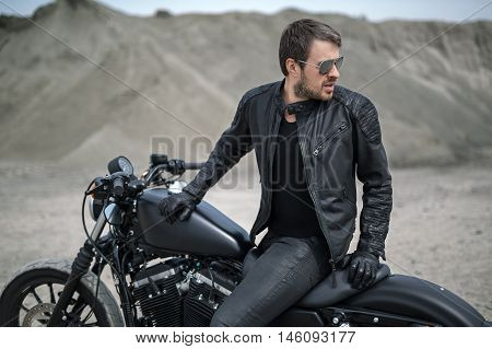Trendy man sits on the black motorbike on the blurry background outdoors. His torso partially turned to the left, hands are on the motorbike. He looks to the left. He wears black jeans, a black T-shirt, black gloves, a black leather jacket and sunglasses.
