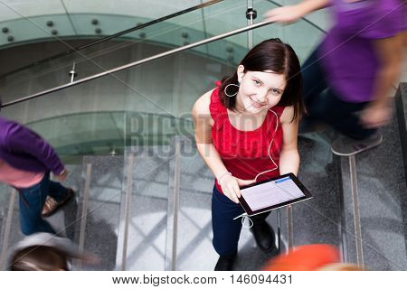 At the university/college - Students rushing up and down a busy stairway - confident pretty young female student with a tablet computer looking upwards (color toned image)