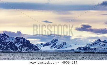 Clouds over mountains covered with snowand glacier in the cold arctic environment in Svalbard.