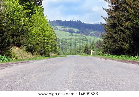 path on the asphalt road through mountains with green fir-trees and grassy valley and road sign