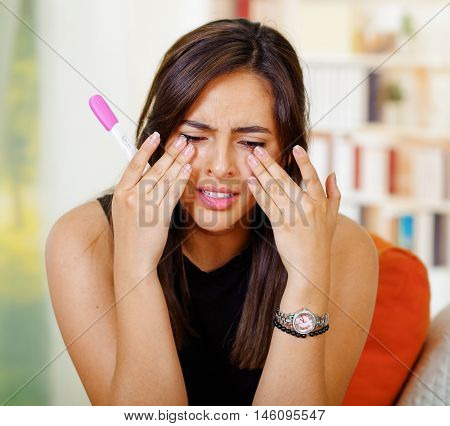 Pretty young brunette woman holding pregnancy home test while wiping tears crying, looking emotional, bookshelves background.