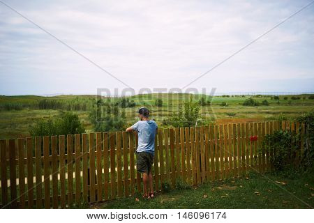 Young Tourist Looking At Green Landscape Standing  A Fence
