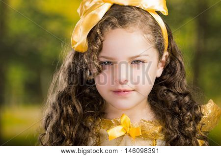Headshot cute little girl wearing beautiful yellow dress with matching head band, posing for camera, green forest background.