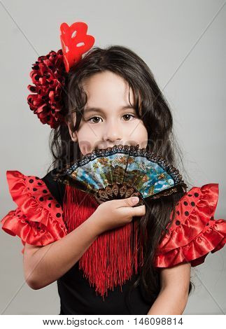 Cute little girl wearing beautiful red and black dress with matching head band, posing for camera using chinese hand fan, studio background.