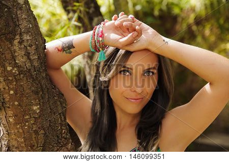 Headshot pretty brunette, standing between trees, bare skinned arms above head pose, sensually looking into camera.