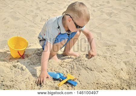 Little boy playing on the beach in the sand. Child sculpts figures out of the sand. Activities in the summer on the sea.