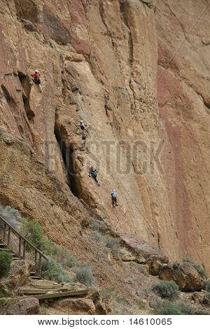 Rock Climbers And Belayers On Sheer Cliff