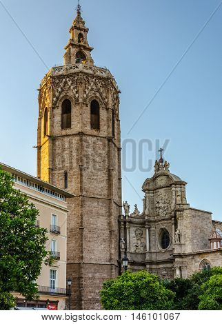 Solemn bell tower in sunlight and part of Cathedral facade in Valencia, summer Spain