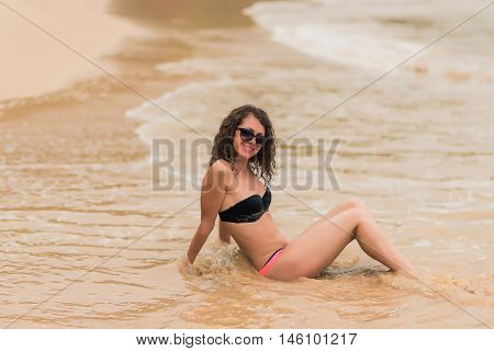 Sexy tanned  fit girl in black bikinii on blue ocean background. Young curly hair woman on the tropical beach.  Woman in bikini at tropical beach.