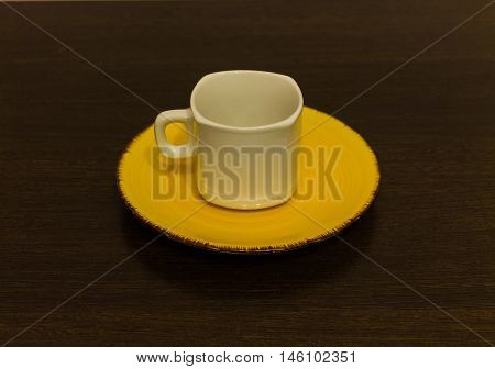 White mug on a yellow plate on a brown table