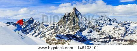 Full length of turn man skiing on fresh powder snow with Matterhorn in background in Swiss Alps.